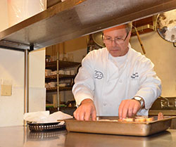 Kitchen Manager John Moos creates croutons.
