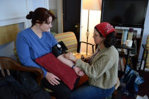 Aspiring certified professional midwives practice using blood pressure cuffs at a midwifery training program at Birth & Beyond in Jamaica Plain. While CPMs do not have all the medical equipment a doctor has in the hospital, they are trained to use basic equipment in order to monitor a laboring woman's health and progress.
