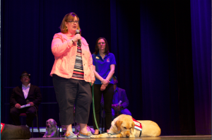 Beth Keane and service dog Beamer are on the NEADS Graduation stage.